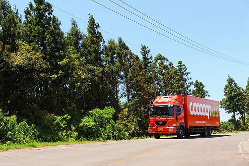 제주희망협동조합의 쿱어스 물류서비스 4.5톤 차량이 도로를 달리고 있는 사진입니다.