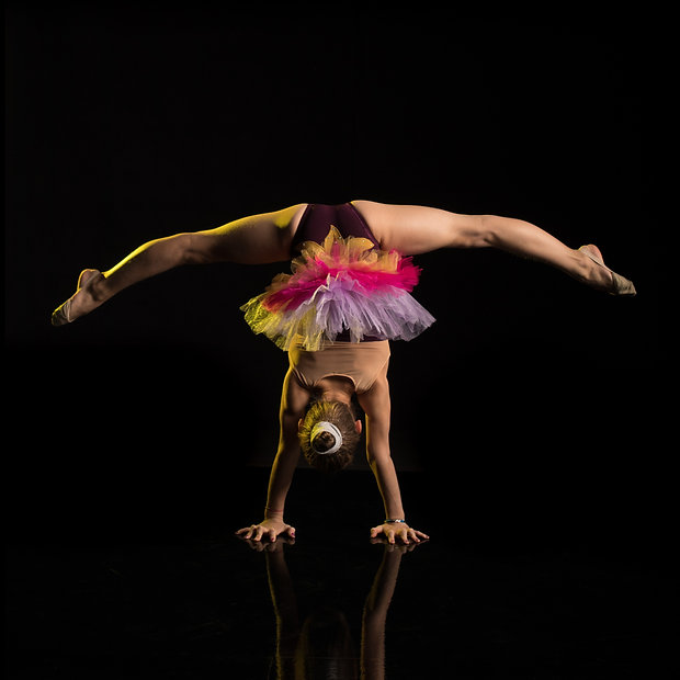 A young girl athlete gymnast performs ac