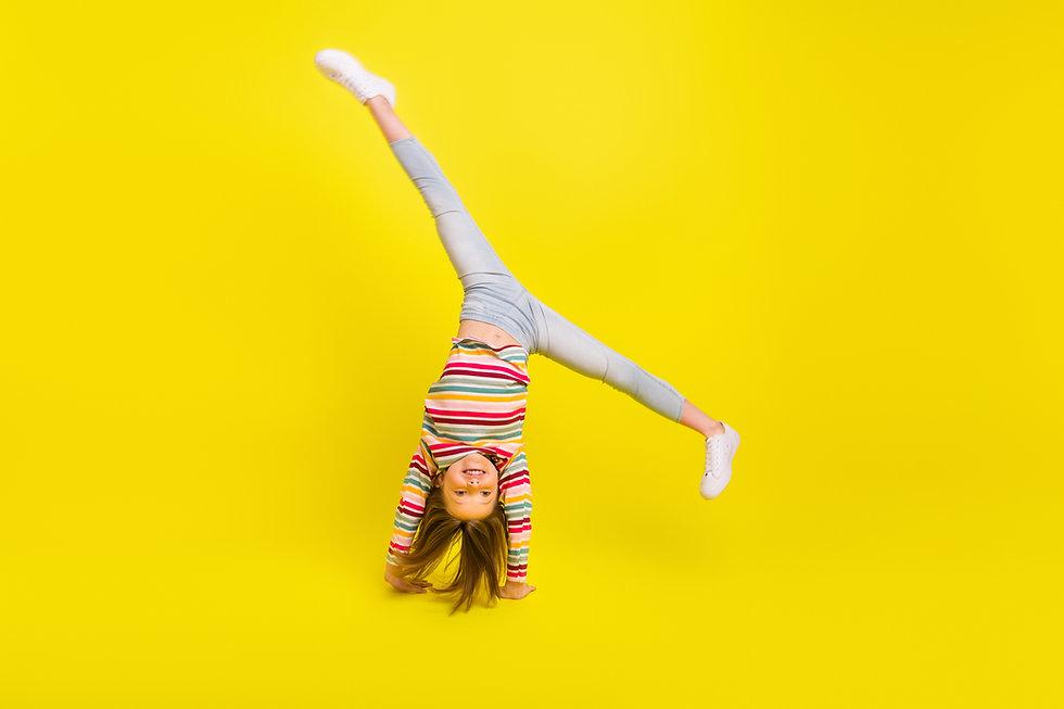 Full length photo of happy flexible little girl enjoy active weekend upside down isolated