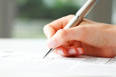 Hand of a caucasian woman holding a silver pen and filling out a form. She's wearing pale pink nail polish.