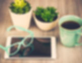 A desktop with two house plants, a cup of coffee, a tablet, and a pair of glasses.