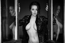 Boudoir photos near me. Woman in black lace open shirt, leaning on a doorway. Miami FL.