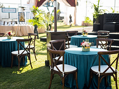 Cocktail table with teal linen, floral arrangement and wood chairs