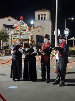 masked carolers with barrier