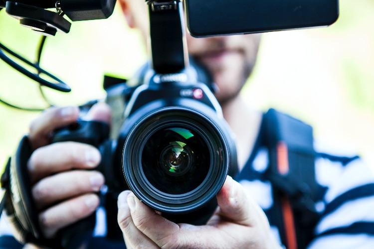 Giovane cameraman intento a fare un video, registrando la scena con attrezzatura professionale