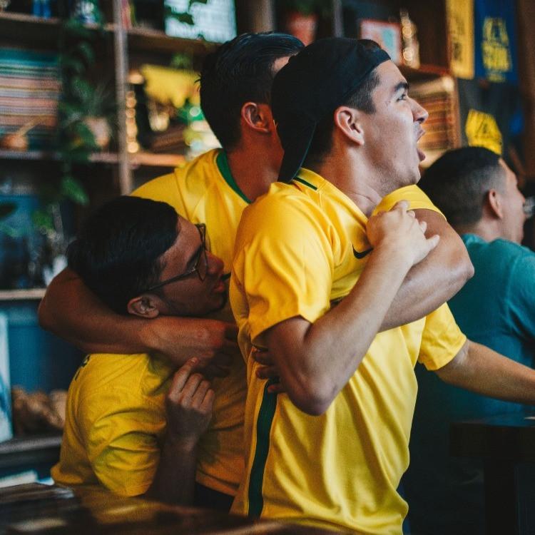 Alcuni amici, tifosi, festeggiano insieme abbracciandosi