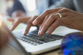 Stock image of a woman typing on a laptop.