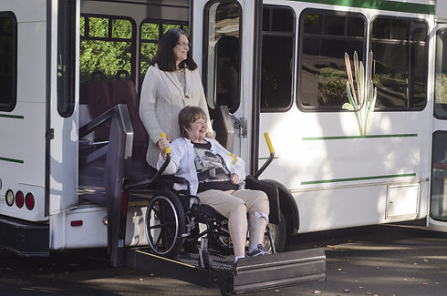 A woman in a wheelchair is helped off a