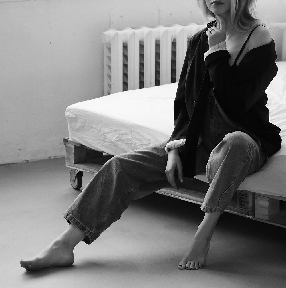 Mulher anônima sentada em cama