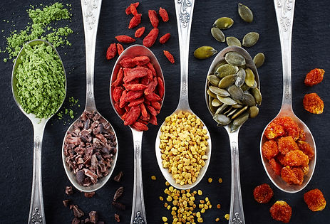 Spoons of various superfoods on black ba