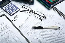 tax forms, calculato, glasses and a pen