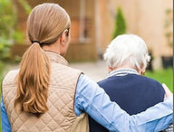 young woman arm around older woman walking away