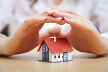 a persons hands covering a small model house