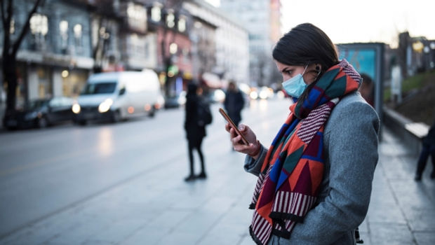 young_woman_with_face_mask_using_smartph