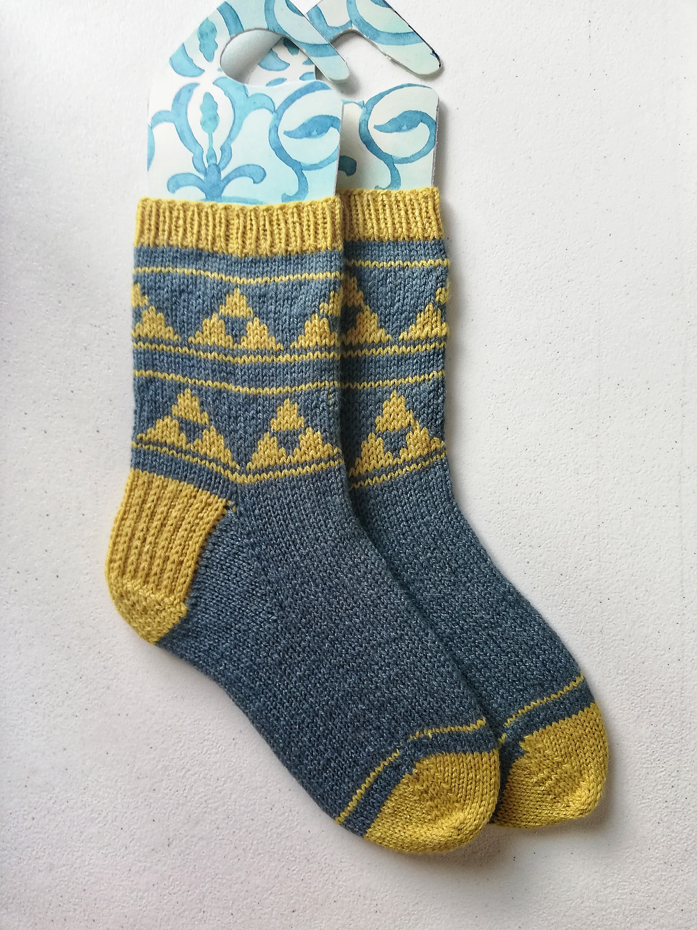 Socks with a triangle motif colorwork pattern on the leg. The cuff, heel, and toe are knit in the contrast color.