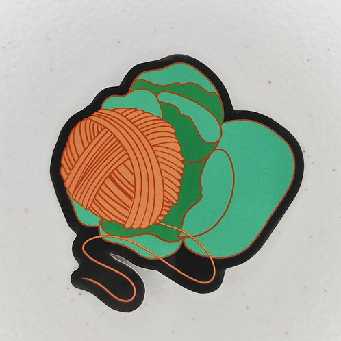 A sticker depicting a yarn ball in the center of a flower.
