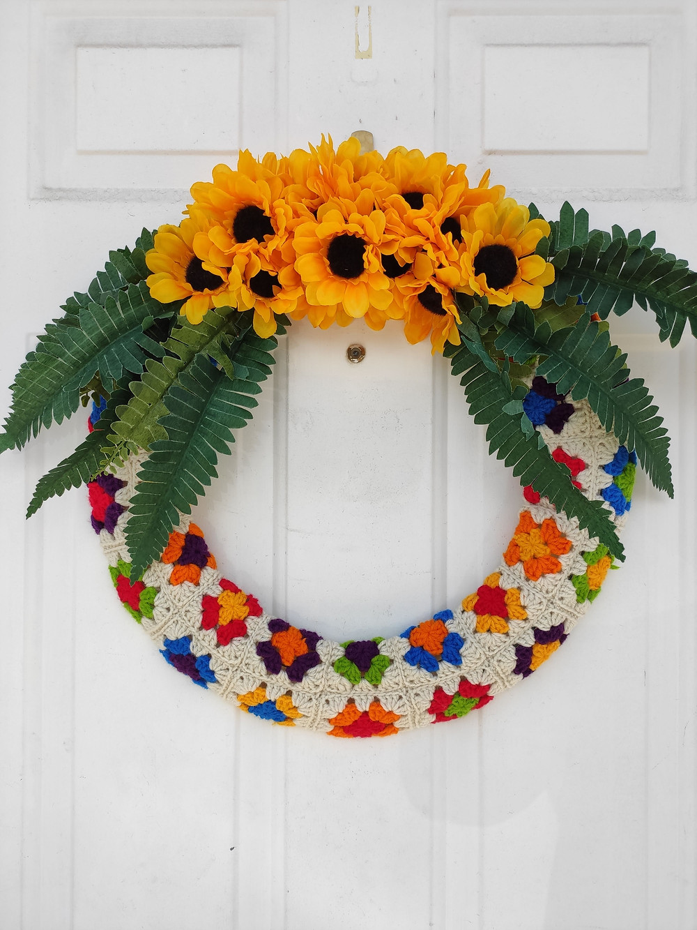 a colorful wreath with fake sunflowers and fake fern leaves glued on the top of the wreath. The rest of the wreath is covered in a colorful granny square fabric.