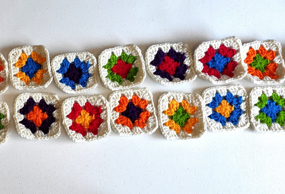 several small multi-colored granny squares lined up side-by-side to determine a good order to sew them in.
