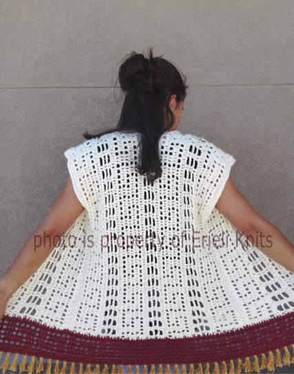 The back view of the Augustus. It is a crocheted, sleeveless cardigan with lace motifs inspired by ancient Rome.