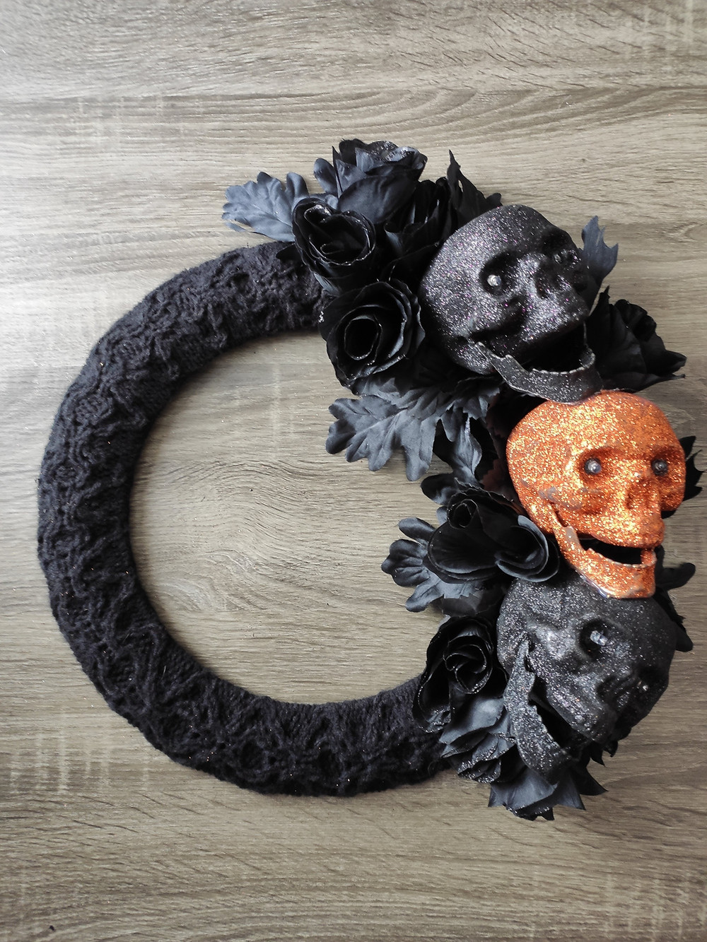 finished wreath. black knit cabled fabric covers about two thirds of the frame. The other third has three glittery skulls surrounded by black flowers.