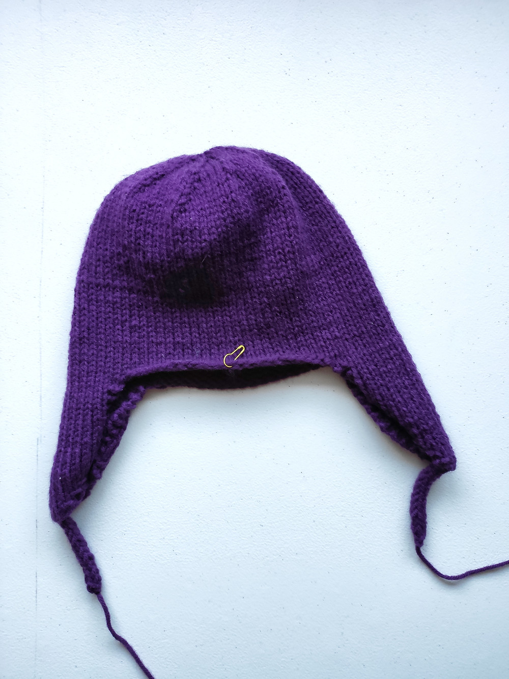 Finished plain earflap hat with short i-cord strings on the ends of the earflaps