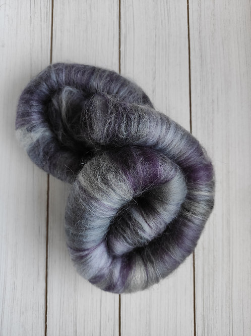 Rolags that are a blend of different purples and greys.