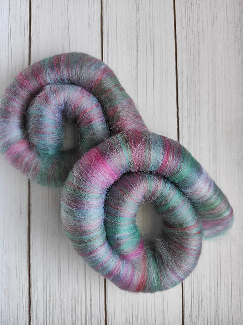 Rolags with a blend of pinks, reds, teals, and white.