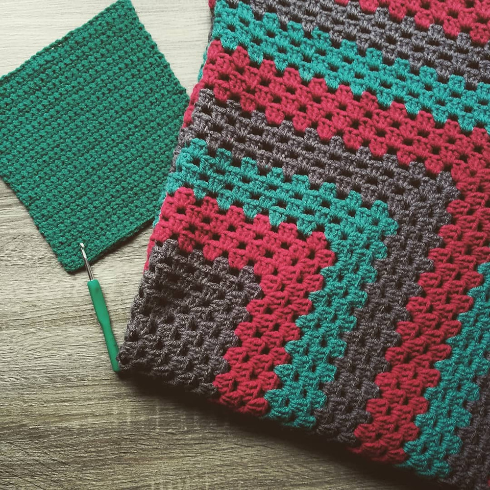 flat lay of a folded, striped, giant granny square that is a lap blanket. There is a crocheted dishcloth next to it.