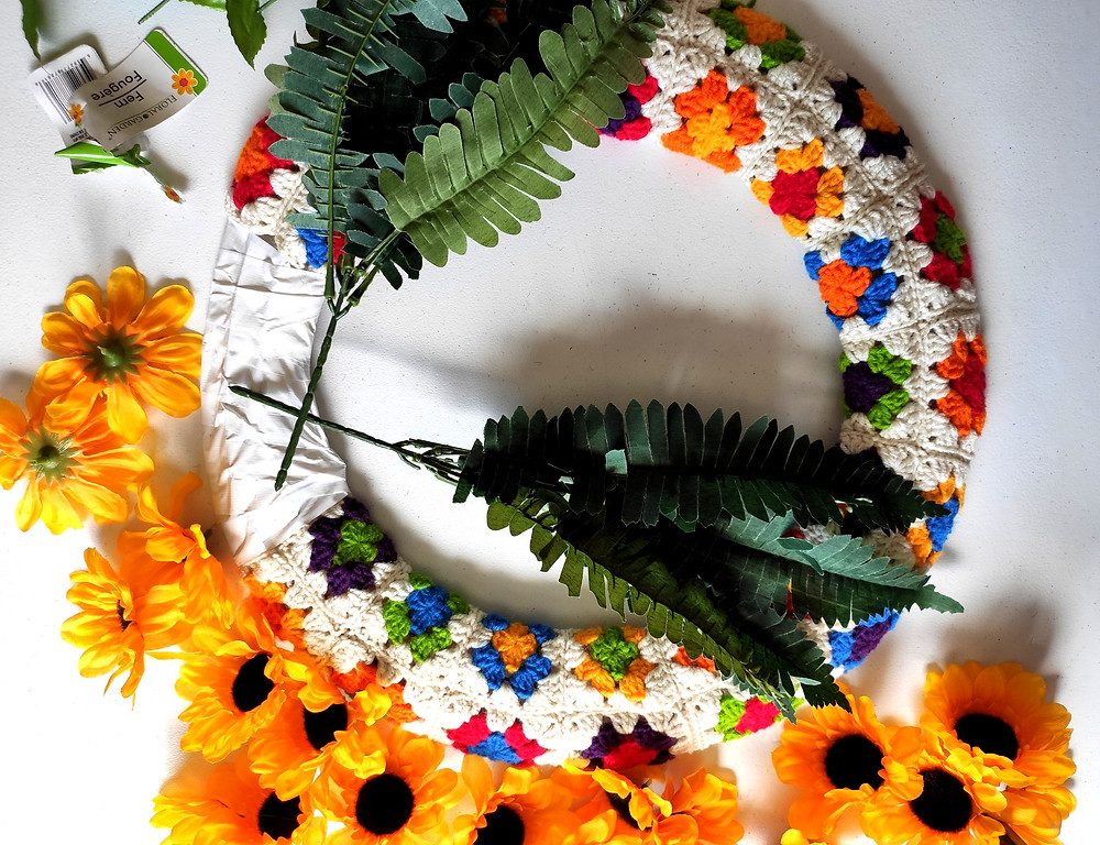 the granny square fabric has been sewn around a circular wreath shape, and fake sunflowers and leaves are waiting to be hot-glued onto the wreath.