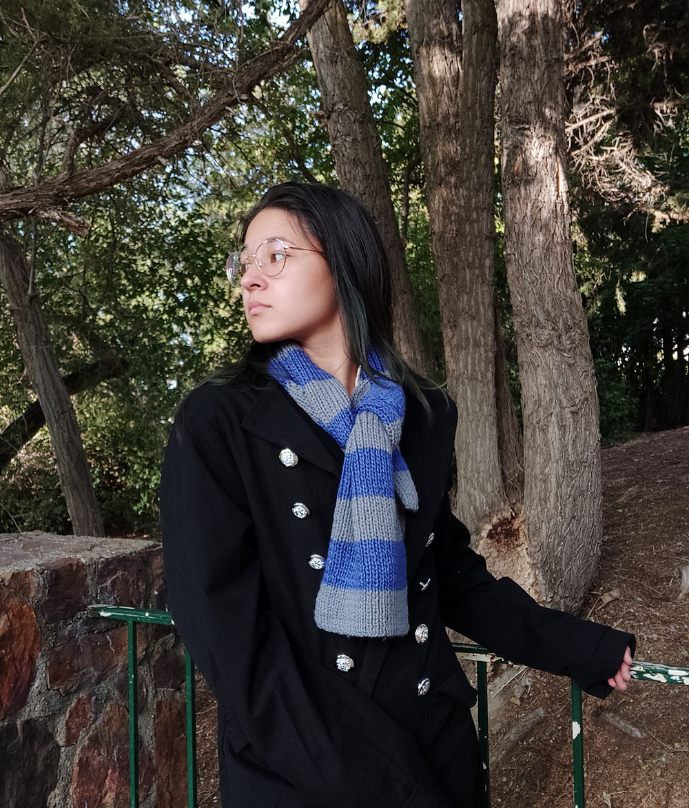 A woman wearing a short blue and grey, striped, hand-knit scarf