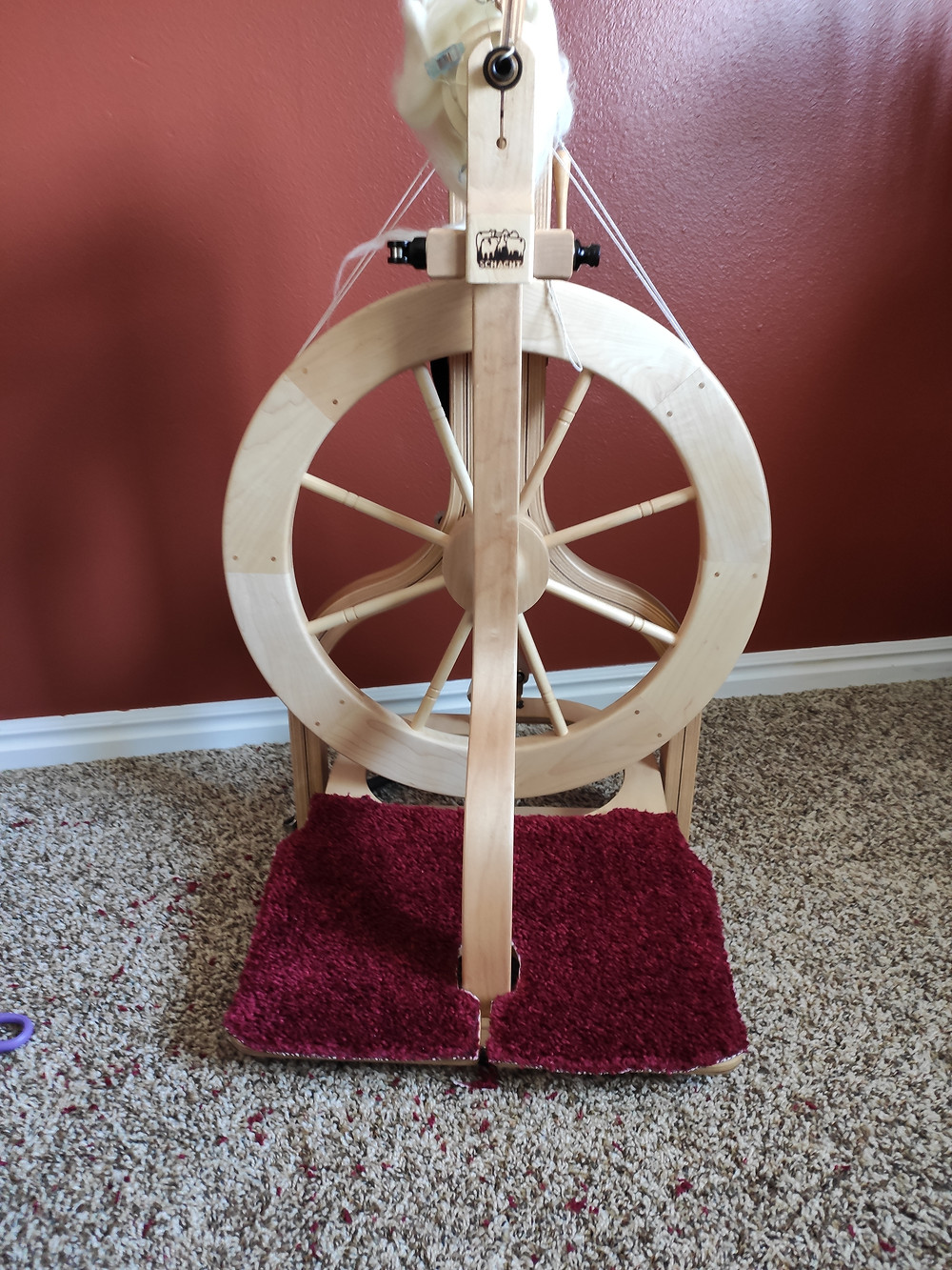 Schacht matchless spinning wheel with finished treadle covers on the treadles.