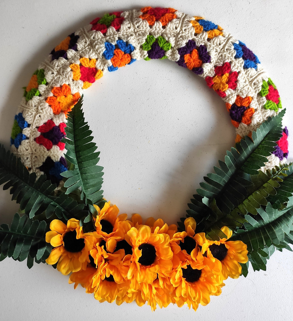 the finished wreath: fake sunflowers are clustered at the bottom, fake fern leaves come out from the sunflowers, and the multi-colored granny square fabric covers the rest of the wreath.