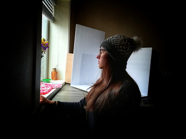 a girl looking out the window wearing the Mamaidh Slouch. The hat has a pompom on it.
