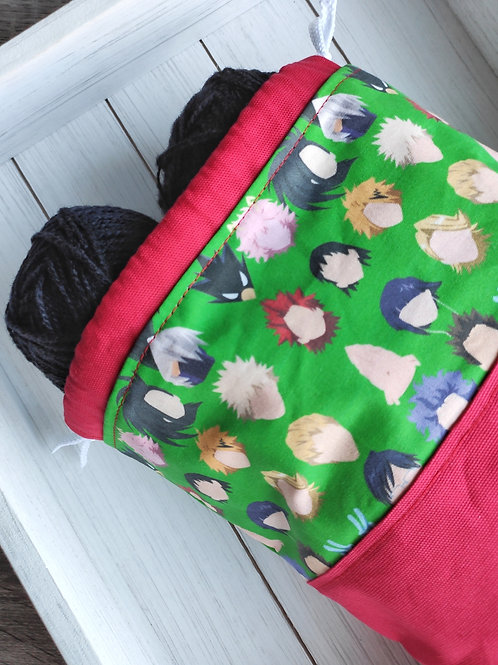 A project bag with a bright red canvas base and a fabric depicting the heads of anime characters on top.