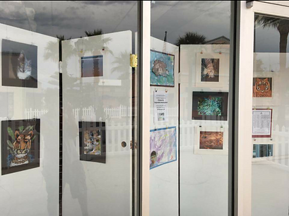 Picture of display of a dozen pieces of student art in Humphries window on Main Street