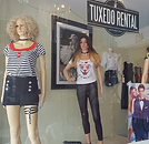 storefront with two casually dressed female mannequins and tuxedo rental sign