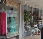 storefront with mannequins in formal gowns