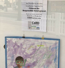 Student art and C4RD signage in Humphries window on Main Street