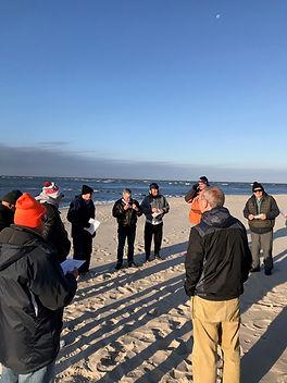 Men's Retreat in November, Men take a walk on the beach bundled up.
