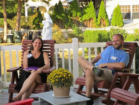 Married Couple Sitting on the Cape Ave porch, a sunny day with Holy Family Statue behind