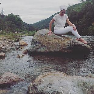 Mujer con turbante vestida de blanco sentada sobre roca en un rio.