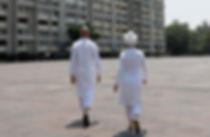 Hombre y mujer de espaldas caminando hacia un conjunto de edificios
