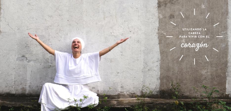 Mujer caucásica con ropa y turbante blancos riendo con los brazos abiertos hacia arriba.