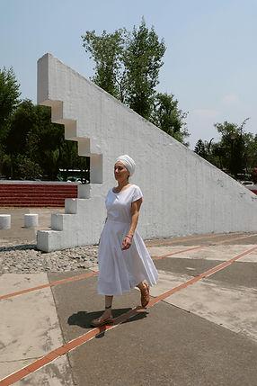 Mujer con vestido y turbante blancos caminando con escultura geomtrica blanca detras.