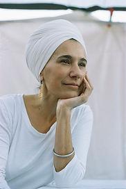 Mujer caucasica con turbante vestida de blanco recargando su barbilla en la mano izquierda mirando a la distancia.