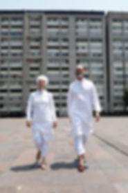 Hombre y mujer de frente caminando desde un conjunto de edificios