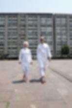 Hombre y mujer caminando hacia la camara lado a lado vesitdos de blanco