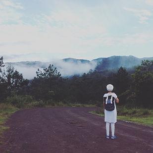 Mujer viendo bosque con neblina a distancia sobre camino de terraceria.
