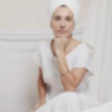 Mujer vestida de blanco con turbante viendo de frente recargando la cabeza en su puño sobre rodilla