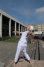 Mujer con ropa y turbante blancos bailando con los ojos cerrados.